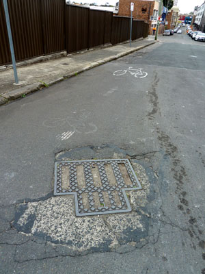 Manhole cover holding together a dilapidated road in Camperdown (Sydney). Photo: meganix 2013.